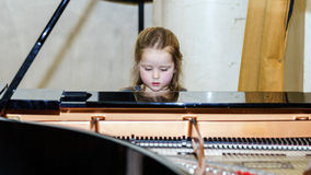 Cute little girl playing grand piano Stock Photos