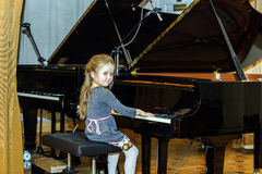 Cute little girl playing grand piano Royalty Free Stock Images