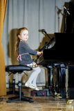Cute little girl playing grand piano Royalty Free Stock Photography
