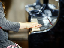 Cute little girl playing grand piano Stock Images