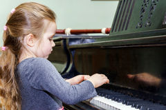 Cute little girl playing grand piano Royalty Free Stock Photos