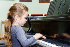 Cute little girl playing grand piano Stock Image