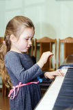 Cute little girl playing grand piano Royalty Free Stock Image