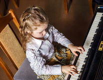 Cute little girl playing grand piano in music school Stock Photos