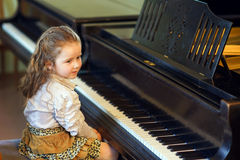 Cute little girl playing grand piano in music school Royalty Free Stock Photos