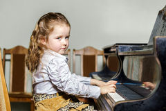 Cute little girl playing grand piano in music school Royalty Free Stock Photo