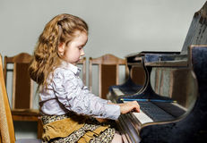 Cute little girl playing grand piano in music school. Childhood concept Royalty Free Stock Image