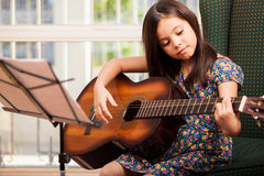 Cute little girl playing the guitar Royalty Free Stock Photos