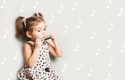 Cute little girl playing harmonica, isolated on white, music education concept stock photo