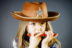 Cute little girl playing harmonica Stock Photos