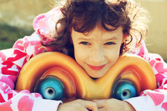 Cute little girl playing and having fun on the playground, in an autumn day. retro filtered image. Royalty Free Stock Image
