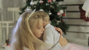 Cute little girl playing with her baby sister near. Cute little girl playing and trying to dance with her baby sister near Christmas tree stock footage