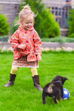 Cute little girl playing with her puppy in the yard Stock Photo