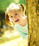 Cute little girl is playing hide and seek. Outdoors Stock Image