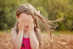 Cute little girl playing hide and seek with camera. Funny little girl playing hide and seek with camera Royalty Free Stock Images