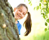 Cute little girl is playing hide and seek. Outdoor shoot Stock Photos