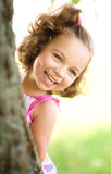 Cute little girl is playing hide and seek. Outdoor shoot Royalty Free Stock Photography