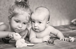 Cute little girl is playing with his younger brother. At home lying on the bed with cups stock images