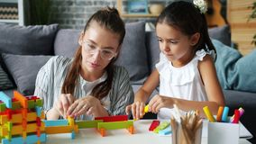 Cute little girl playing at home with caring mother having fun with wooden toys