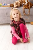 Cute little girl playing at home on floor smiling Stock Photography