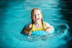Cute little girl playing with inflatable ring in indoor pool. Child learning to swim. Kid having fun with water toys. Royalty Free Stock Images