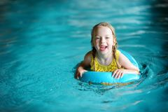 Cute little girl playing with inflatable ring in indoor pool. Child learning to swim. Kid having fun with water toys. Royalty Free Stock Photo