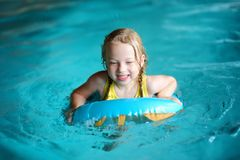 Cute little girl playing with inflatable ring in indoor pool. Child learning to swim. Kid having fun with water toys. Stock Photos