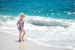 Cute little girl playing jumping over the waves Stock Photos