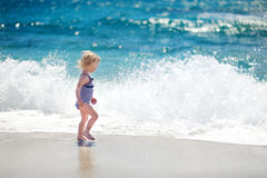 Cute little girl playing jumping over the waves Royalty Free Stock Photography