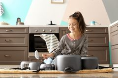 Cute little girl playing with kitchenware. As drums in kitchen stock photo
