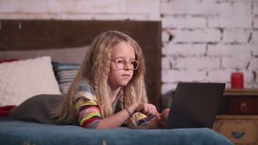 Cute little girl playing with laptop on the bed stock video footage