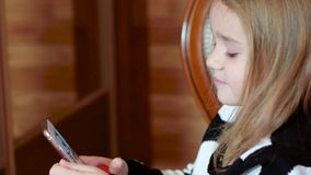 Cute little girl playing with a mobile phone, the girl opens the application on the gadget, playing mobile games, speaks stock footage