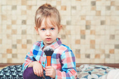 Cute little girl playing with mommy`s make up. Toned. stock photos