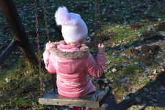 Cute little girl playing near the lake in the autumn park. Cold temperature royalty free stock image