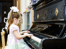 Cute little girl playing old piano Royalty Free Stock Images