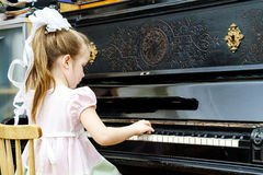 Cute little girl playing old piano Royalty Free Stock Image