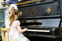 Cute little girl playing old piano Stock Photography