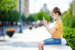 Cute little girl playing outdoor mobile game on her smart phone Stock Images