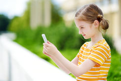 Cute little girl playing outdoor mobile game on her smart phone Royalty Free Stock Photos