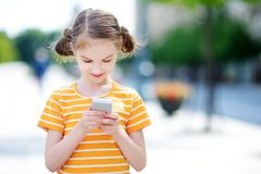 Cute little girl playing outdoor mobile game on her smart phone. Kid catching virtual pocket monsters. Modern addictive multiplayer location-based games Royalty Free Stock Image