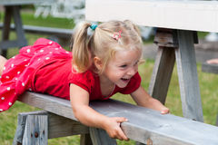 Cute little girl playing on a park bench Royalty Free Stock Photos