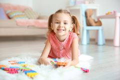 Cute little girl playing with pazzles. At home Stock Photos