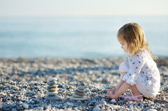 Cute girl playing on pebble beach Stock Photo