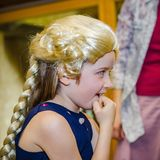 Cute little girl playing piano, dressing in retro Mozart periwig stock photo