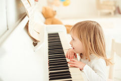 Cute little girl playing piano in light room. Royalty Free Stock Image