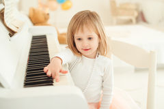 Cute little girl playing piano in light room. Royalty Free Stock Photography