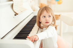Cute little girl playing piano in light room. Stock Images