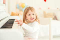 Cute little girl playing piano in light room. Royalty Free Stock Photos
