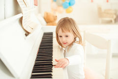 Cute little girl playing piano in light room. Stock Photos