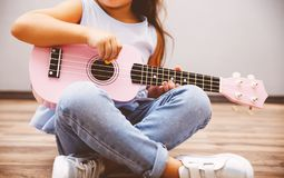 Cute little girl playing pink ukulele sitting on floor. Cute little girl in smart fashiony clothes playing pink ukulele sitting on floor stock images
